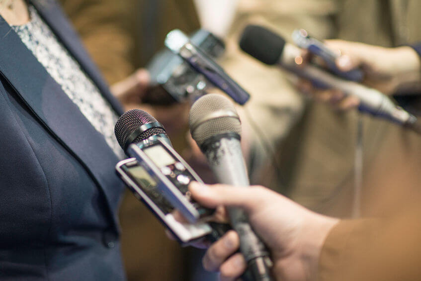 57134905 - group of journalists interviewing politician, holding microphones and voice recorders